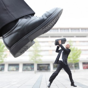 128748504-giant-foot-stepping-on-male-executive-gettyimages